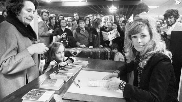 Vivi Bach an Tisch mit Kinderbuch vor sich liegend. Mutter mit kleinem, aufgeregten Mädchen schauen ihr dabei zu, wie sie das Buch signiert.