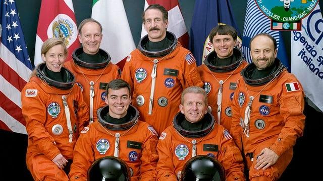 Sechs Astronauten und eine Astronautin tragen auf dem Gruppenbild orange Weltraumanzüge.