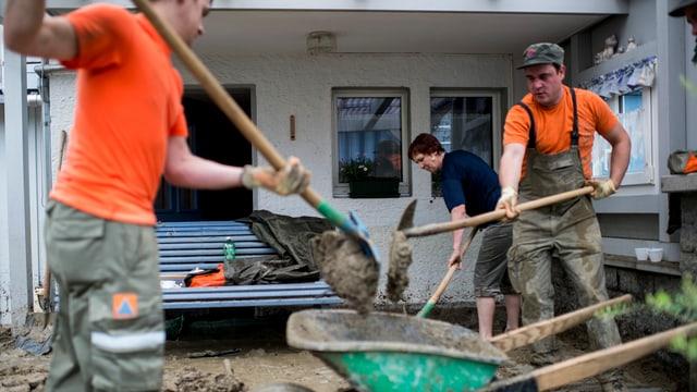 Zwei Zivilschutzarbeiter helfen bei einer Überschwemmung