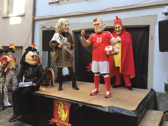 Bühne während der Luzerner Fasnacht, auf der maskierte Fasnächtler ein Theater aufführen.