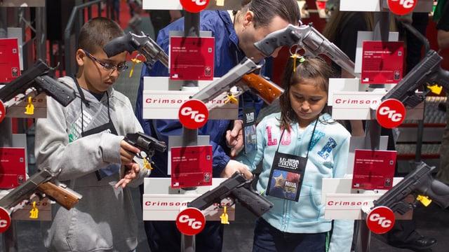 Kinder mit Eltern in einem Waffengeschäft in den USA.
