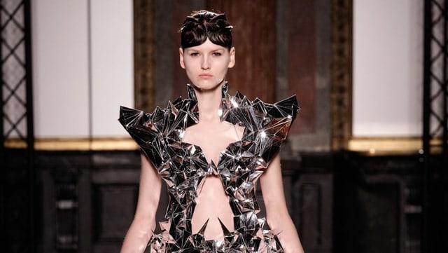 Model auf dem Laufsteg in einem Kleid aus Spiegeln