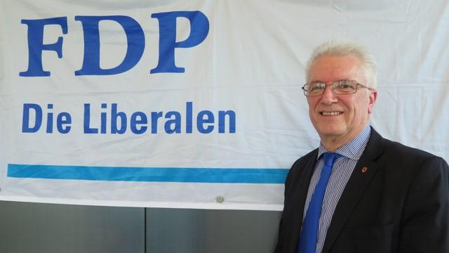 Pierre-Yves Grivel vor einem Transparent der FDP.