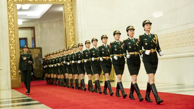 Eine Reihe Soldatinnen in Uniform auf rotem Teppich, sie proben für die 70-Jahr-Feier.