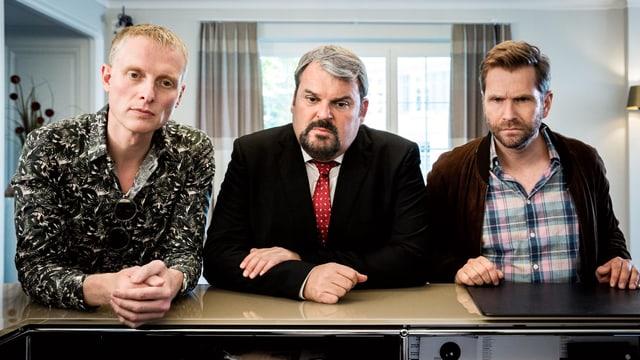 Drei Männer lehnen auf einer Theke und gucken ernst.