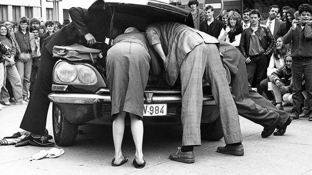 Ein Theaterstück: Leute schauen unter die Motorhaube eines Autos. Im Hintergrund: Publikum.