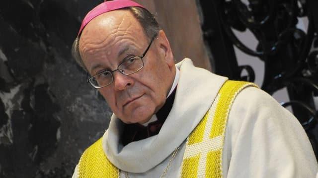Bischof Huonder in einem weiss-gelben Gewand blickt skeptisch nach links.