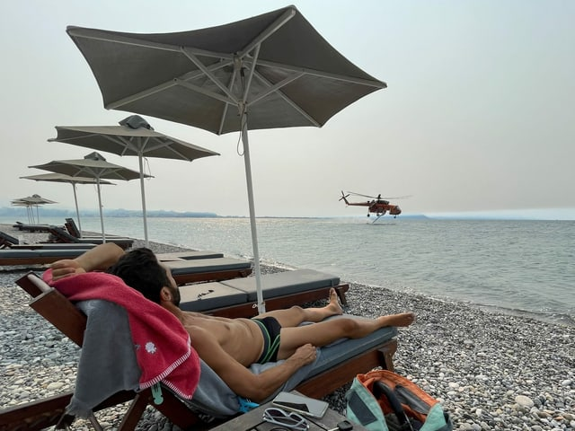 Qualcuno è al sole su una sedia a sdraio sulla spiaggia mentre fa rifornimento sullo sfondo di un elicottero.