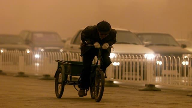 Velofahrer und Autos in einem Sandsturm.