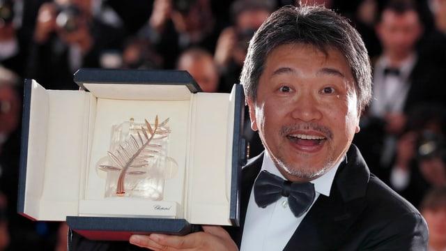 Ein Mann in Anzug mit freudigem Lachen hält eine Schachtel, in der ein goldenes Blatt liegt.