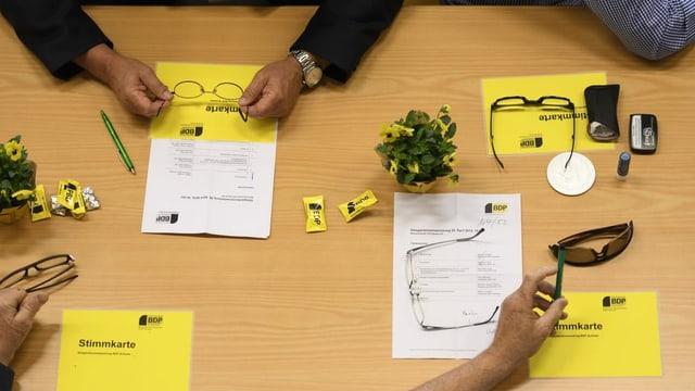 Blick von oben auf einen Tisch mit gelben Stimmkarten