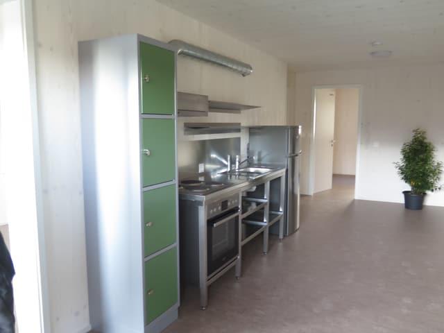 Ein heller Boden, ein Gestell mit grünen Schranktüren, ein Kochherd und ein Abwaschbecken. Einfache Küche.