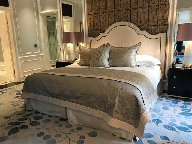 Ein riesiges Bett in beige-grünen Farben. Ein heller Teppich mit einem Muster mit blauen Blättern.