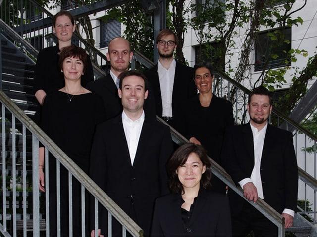 Die in Schwarz-Weiss gekleideten Sängerinnen und Sänger posieren fürs Gruppenbild auf einer Treppe.