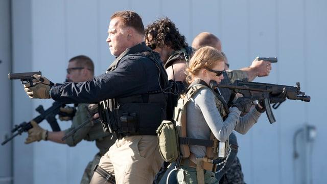 Ein bewaffnete Gruppe von Menschen Rücken an Rücken.