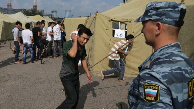 Soldat im Vordergrund. Im Hintergrund asiatische Migranten und Zelte.
