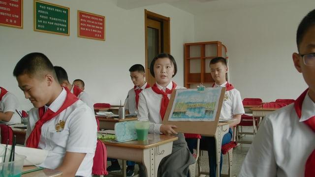 Ein Klassenzimmer. Asiatische Kinder in Schuluniform. Ein Mädchen zeigt eine Zeichnung eines Berges.