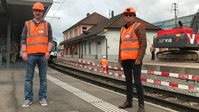 Zwei Männer in orangen Warnwesten stehen auf einem Perron vor dem WSB-Bahnhof in Aarau.