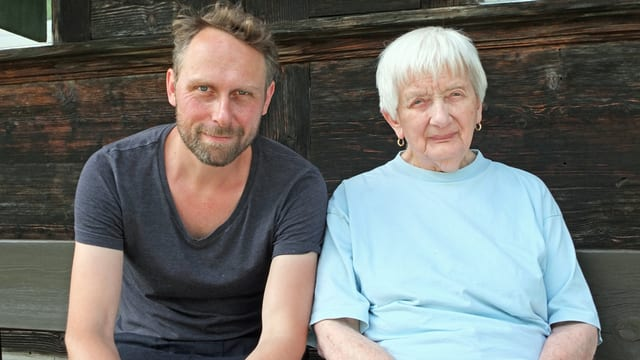 Mann neben alter Frau auf Bank vor Holzhaus.
