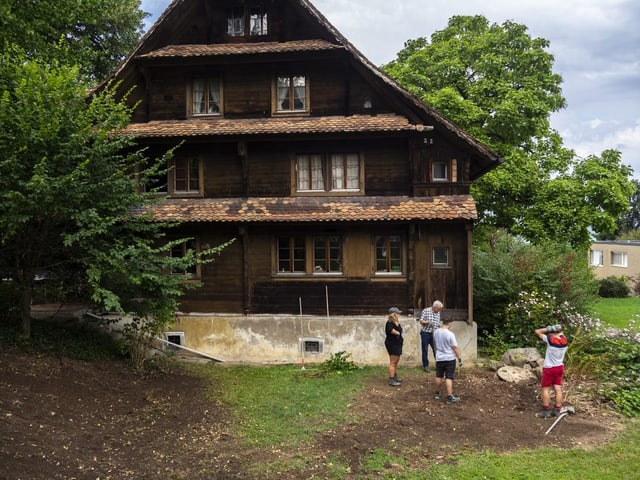 Ein altes Haus in Zug, vier Personen stehen davor im Garten.