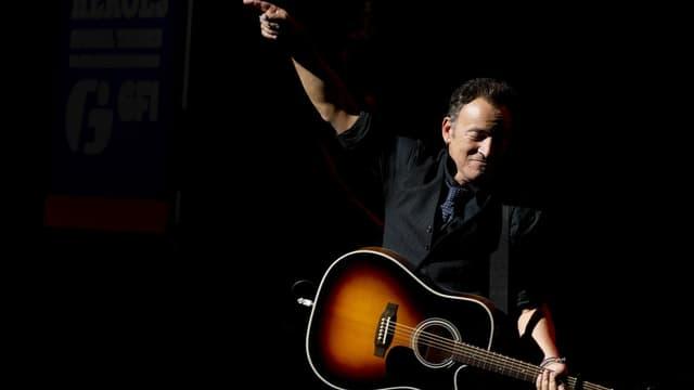 Mann mittleren Alters steht mit Gitarre auf der Bühne