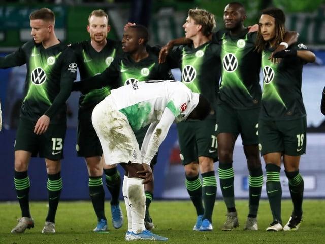 Breel Embolo ärgert sich nach Gladbachs 1:2-Niederlage, während die Wolfsburg-Spieler feiern.