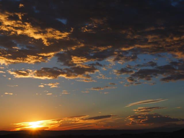 Sonnenaufgang, von oben her nähern sich dunkle Wolken.