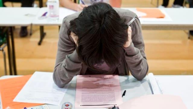 Ein schwarzhaariger Mann sitzt über eine Prüfung gebeugt.