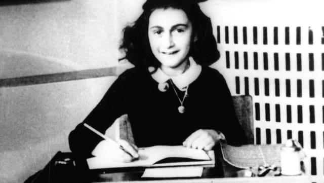 Anne Frank sitzt an einem Tisch und schreibt.