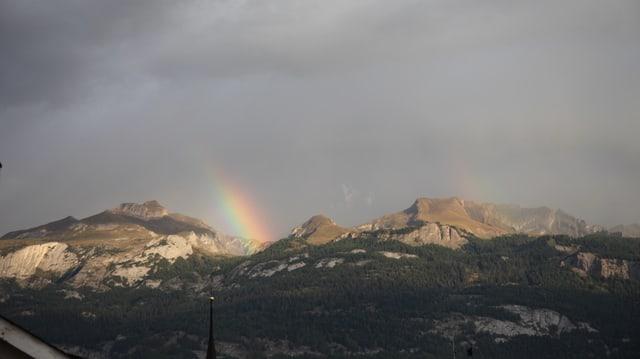 Blick hinauf zu Bergen mit einem Ansatz von einem Regenbogen. Über den Bergen viele Wolken.