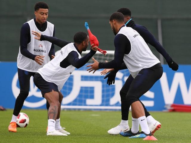 Die England-Spieler werfen sich ein Gummihuhn zu.