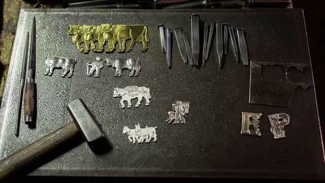 Fein  bearbeitete Kühe und Geissen aus Silber und Messing, Nägel und ein Hammer.