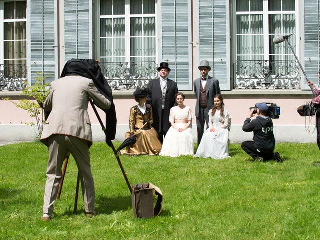 Fotograf fotografiert Familie Thaler im Garten vor Villa