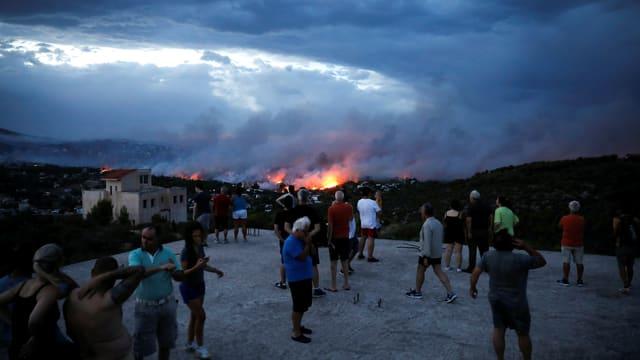 Menschen beobachten von einem Hügel das Feuer