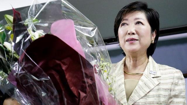 Japanische Frau hält einen Blumenstrauss in der Hand und lächelt.