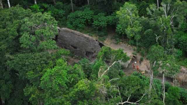 Luftbild mit Indigenen, die in einem Urwald leben. Zu sehen sind einfache Hütten und Menschen.
