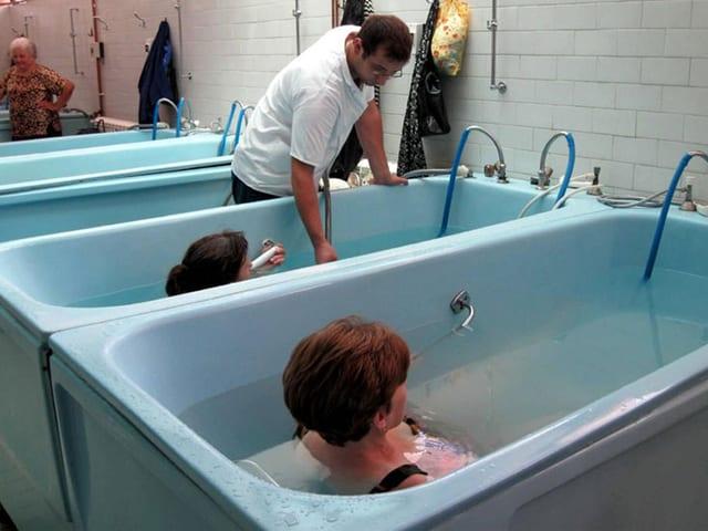 Zwei Frauen in grossen Badewannen. Ein Mann in weissem T-Shirt fügt der einen Wanne mehr Wasser zu.