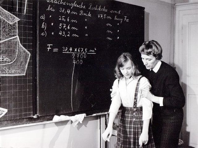 Ein Mädchen steht in einem Schulzimmer vor der Wandtafel. Hiter ihr steht ein Lehrer, der es an beiden Oberarmen festhält.