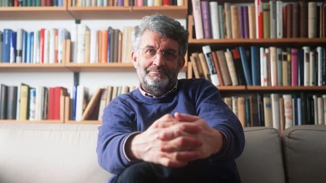 Ulrich Knellwolf sitzt auf einem Sofa vor einem Bücherregal.
