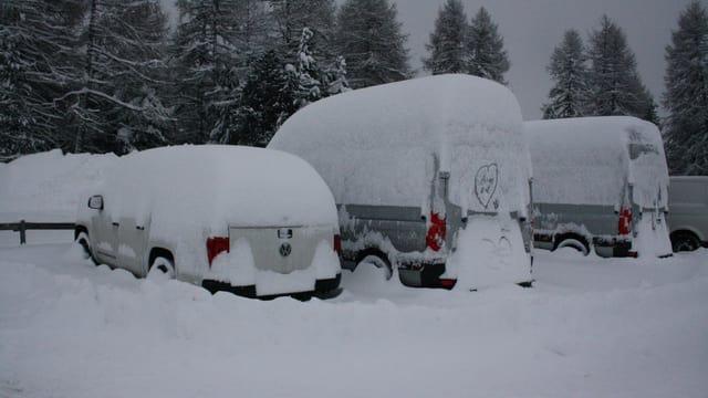 Tief verschneite Fahrzeuge in Salastrains im Engadin.