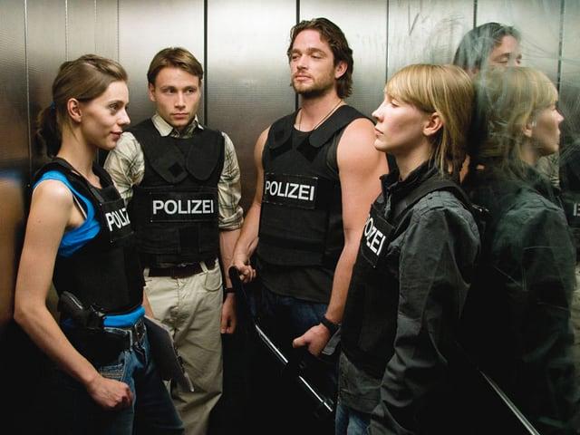 Zwei Polizistinnen und zwei Polizisten in einem Aufzug.