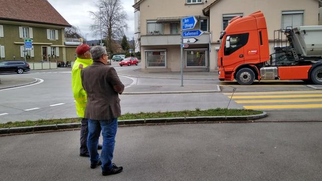 Zwei Männer stehen an einer Strasse