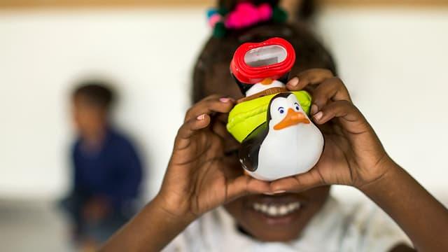 Schwarzes Mädchen hält Plastikspielzeug in die Kamera