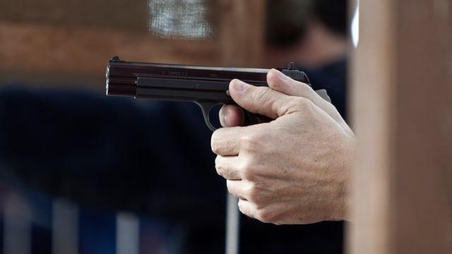 Hand hält Pistole.