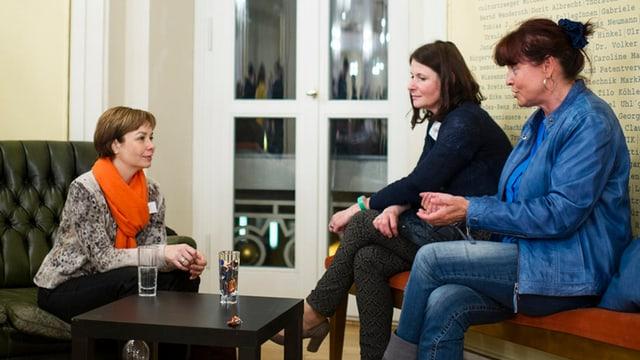 Drei Frauen sitzen um einen Tisch