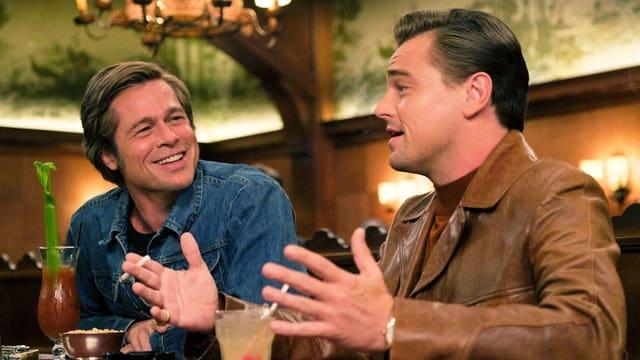 Brad Pitt und Leonardo DiCaprio sitzen in einer Bar und trinken Cocktails.