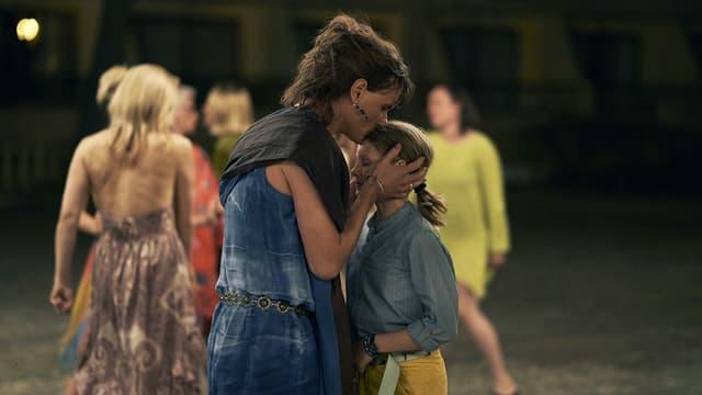 Filmszene: Auf der Tanzfläche küsst eine Frau ein Mädchen auf die Stirn.