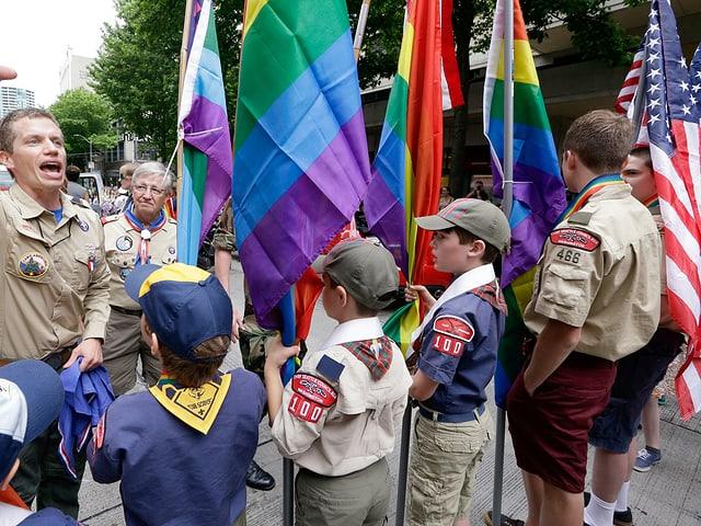 Ein Pfadfinder-Leiter und ein paar Jugendliche mit USA- und Regenbogenfahnen.