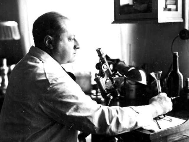 Gottfried Benn im Arztkittel, sitzend vor einem Mikroskop.