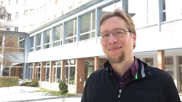 Björn Rasch vor einem Gebäude.
